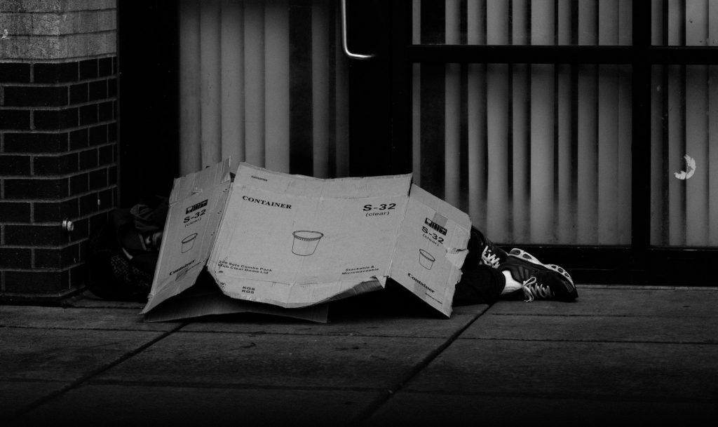 Das Foto zeigt einen Obdachlosen auf der Straße liegend. Foto von THE COLLAB. von Pexels