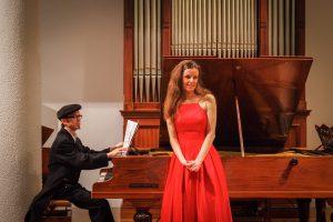 Das Foto zeigt einen Klavierspieler und eine Sängerin im roten Kleid.