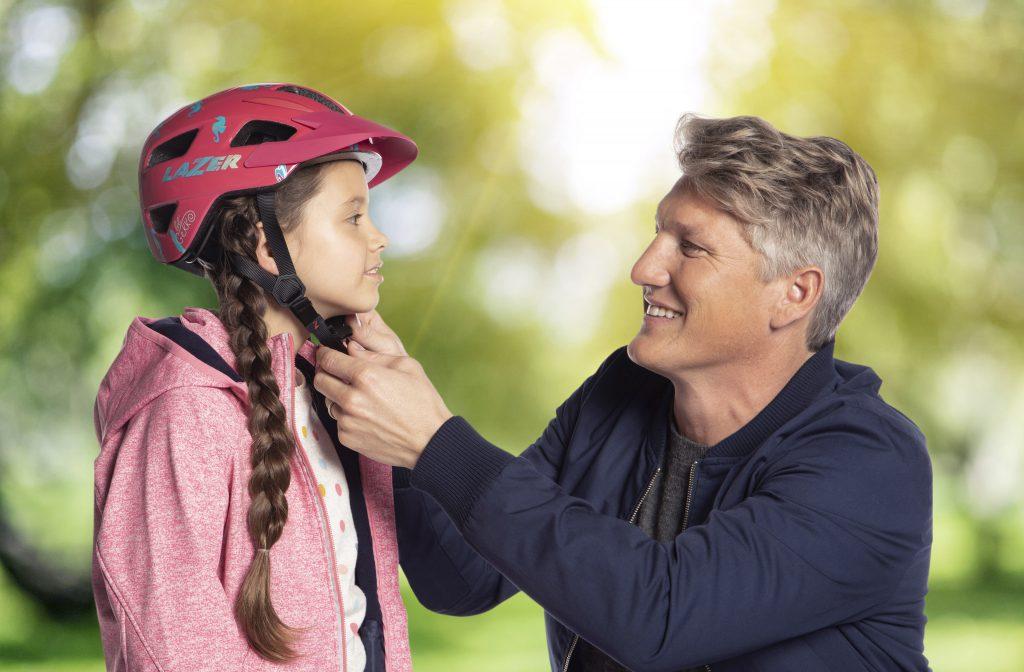 Bastian Schweinsteiger schließt den Fahrradhelm eines Mädchens. Foto: KettlerPR