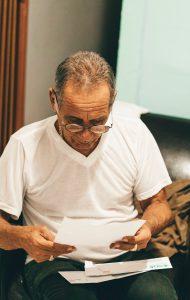 Foto von One Shot von Pexels-of-old-man-reading-paper Mann liest Rentenbescheid