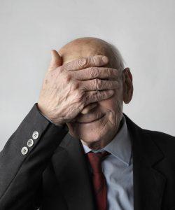 Das Foto zeigt einen älteren Mann, der sich die Hand vor die Augen hält.