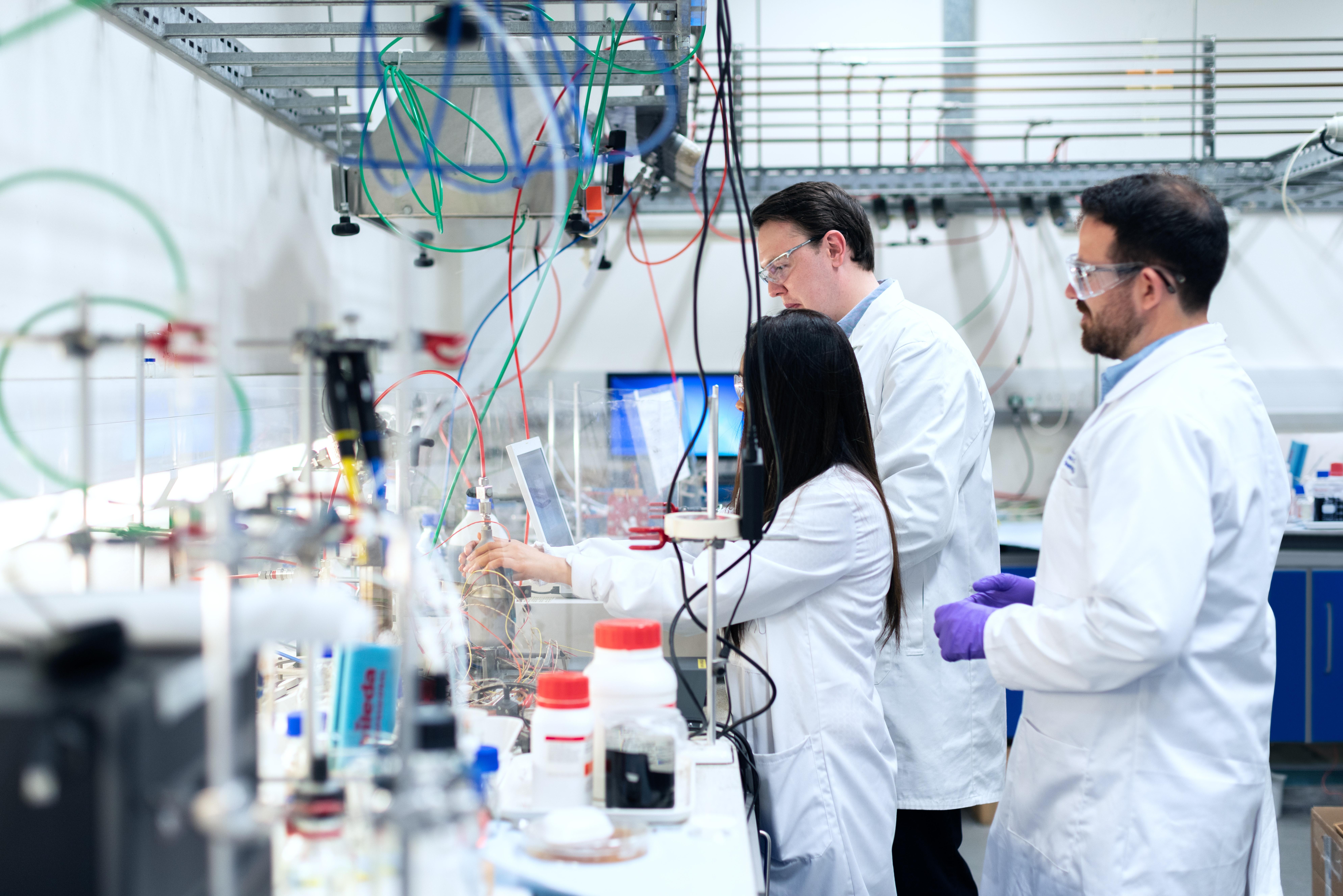 Das Foto zeigt ein Labor. Zwei männliche und eine weibliche Wissenschaftlerin