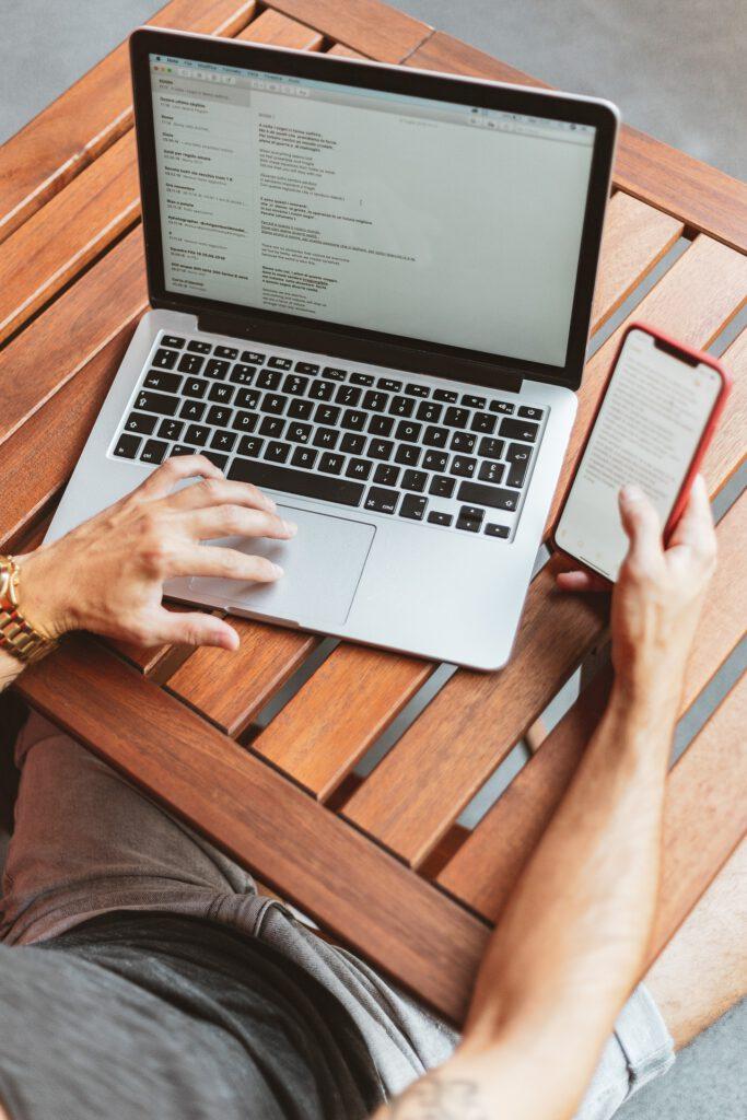 Das Foto zeigt eine Person am Laptop und Smartphone arbeiten