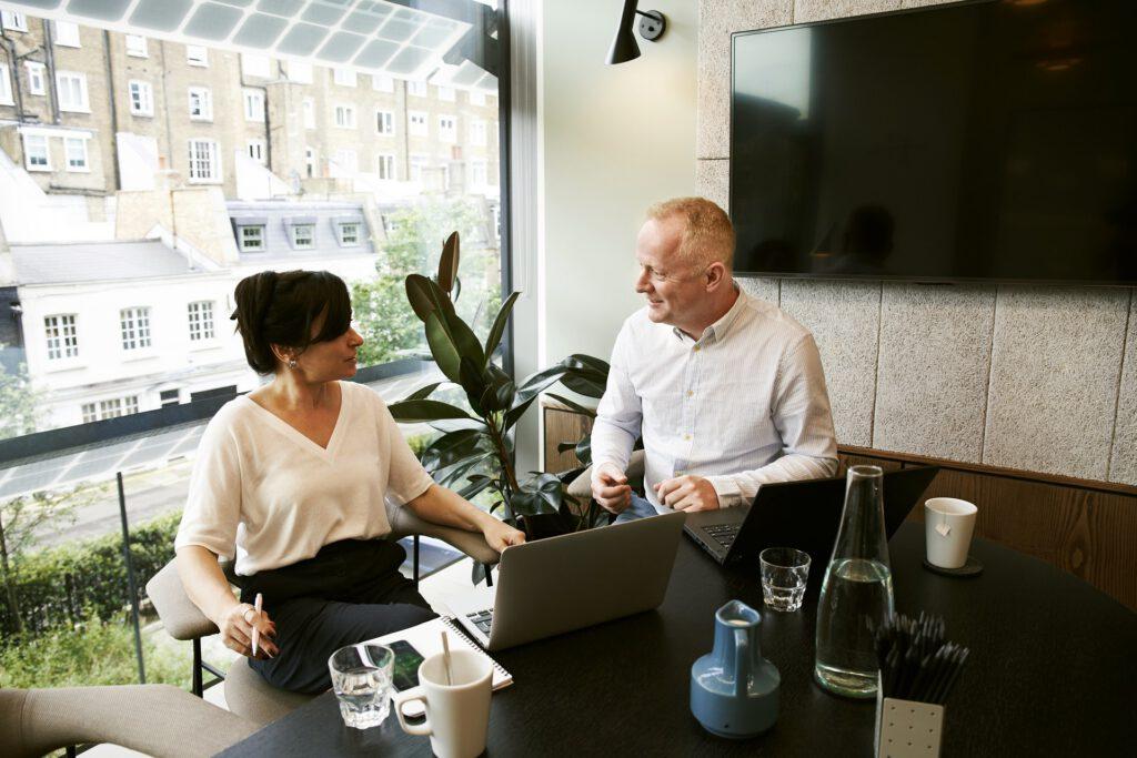 Das Foto zeigt eine Frau und einen Mann bei der Arbeit am Computer.