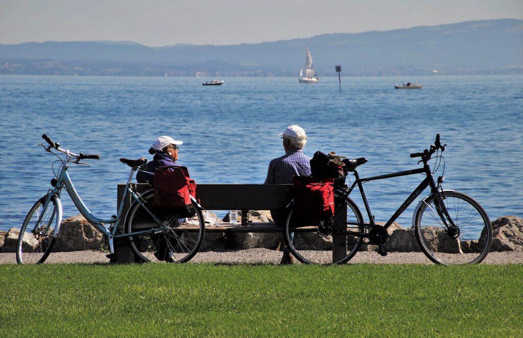 2 Radler sitzen auf der Parkbank und schauen auf die Ostsee