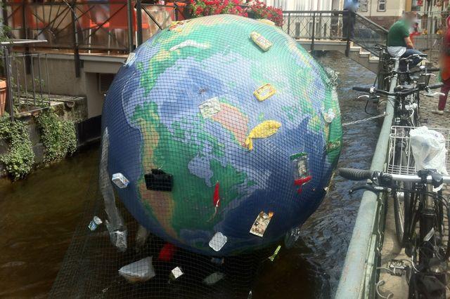 Erdball mit Müll, um zu zeigen, dass die Umwelt leidet.